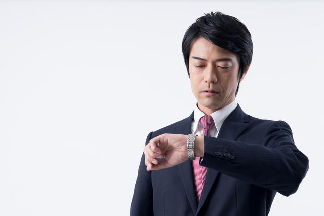 腕時計を確認する中年男性